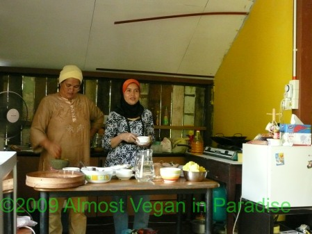 Ibu Zalehan pounds curry paste, while Ibu Asiah explains.