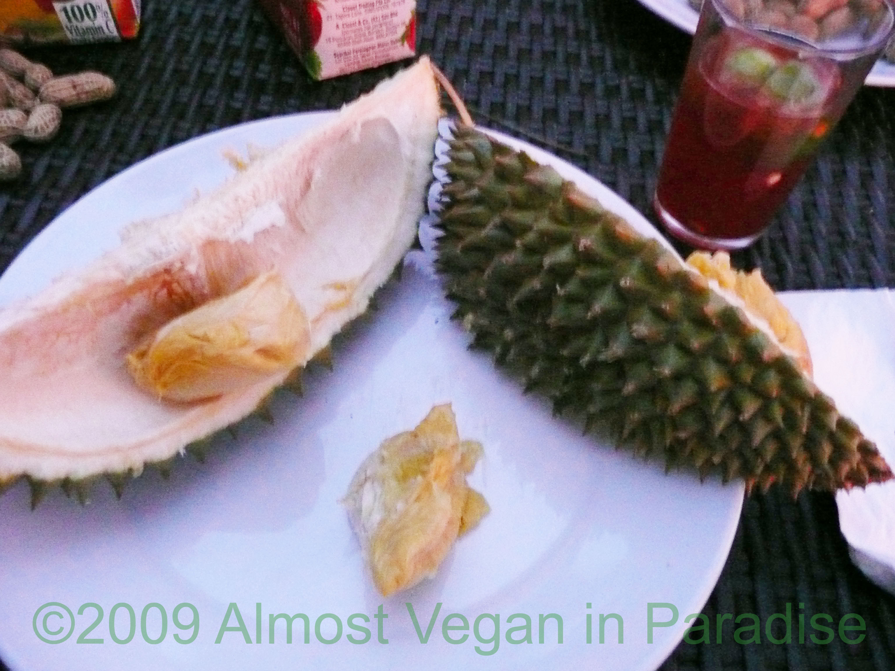 Spiny durian cut into wedges, exposing edible chunks of creamy fruit.