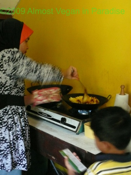 "Ibu Asiah stirs pineapple curry while her son, Azam, asks, ""What step are you on, Mama?"""